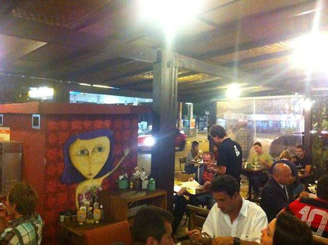 Parte externa do café com a arte de Aêvog Oluap entre as mesas